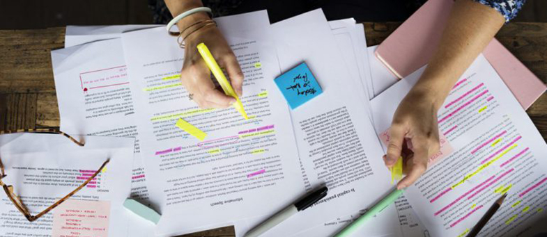 hands highlighting pages of writing post its