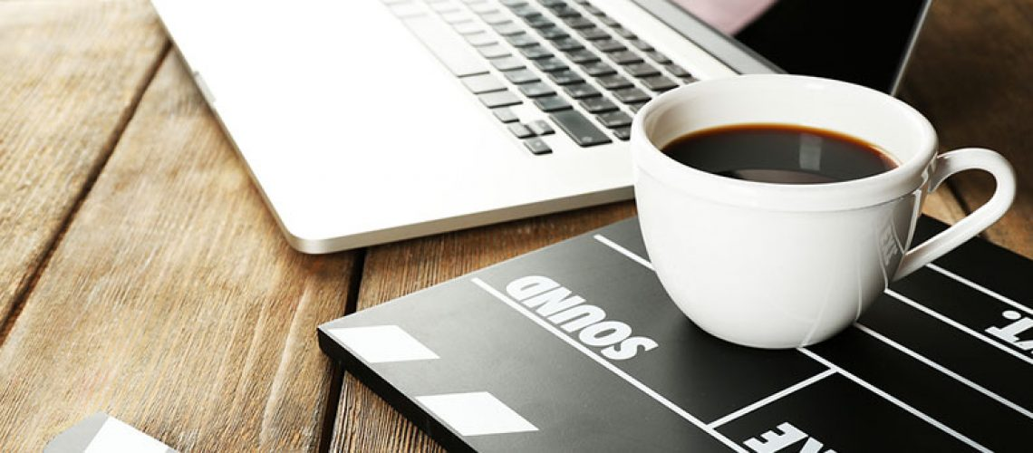 coffee sitting on clapperboard nest to laptop