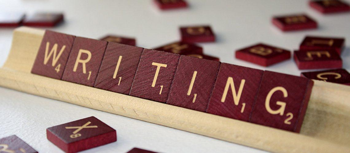 brown scrabble tiles spelling writing