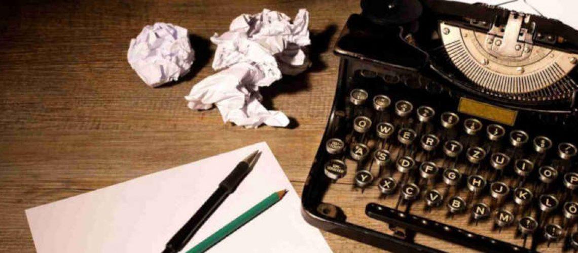 vintage typewriter on desk scrunched up paper pens