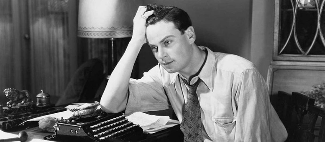 man looks frustrated leaning on typewriter black and white